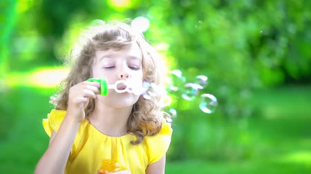 bright bubble : Happy child blowing soap bubbles in spring park. Kid having fun outdoors. Imagination and freedom concept. Slow motion from 120 fps