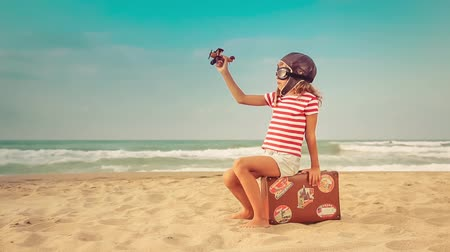 Happy child playing on the beach with toy airplane. Kid against summer sea and sky background. Travel and vacation concept 影像素材