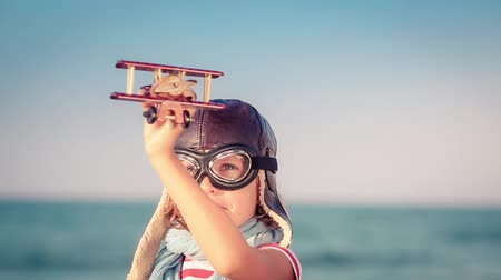 Happy child playing with toy airplane. Kid against summer sea and sky background. Travel and vacation concept
