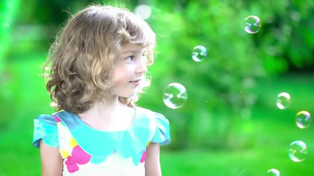 Happy child blowing soap bubbles in spring park. Kid having fun outdoors. Imagination and freedom concept. Slow motion from 120 fps