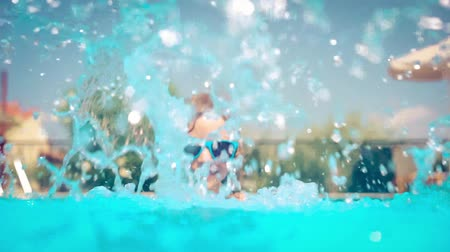 Happy child playing in swimming pool. Girl having fun outdoors. Summer vacation and holiday concept. Slow motion 影像素材