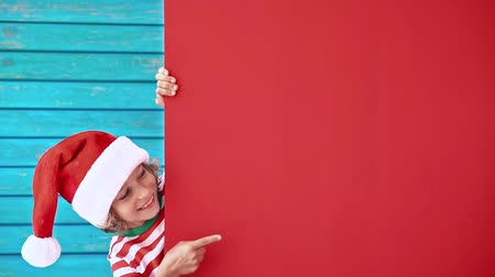 hiding : Happy child holding red Christmas banner blank