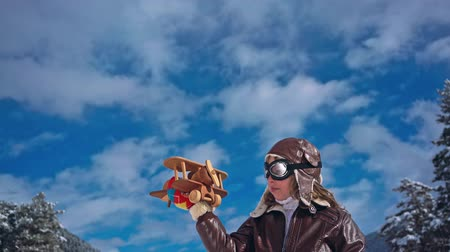 aspirace : Happy child playing with wooden airplane against winter sky background Dostupné videozáznamy