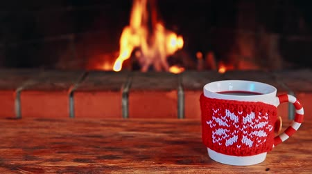 камин : Cup of mulled wine against fireplace