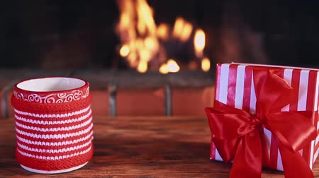fireside : Christmas gift and cup of mulled wine against fireplace Stock Footage