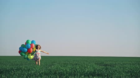 Happy child playing with bright multicolor balloons outdoor. Kid having fun in green spring field against blue sky background. Healthy and active lifestyle concept 影像素材