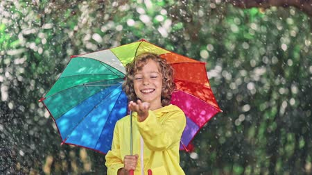 Happy child playing in the rain 影像素材