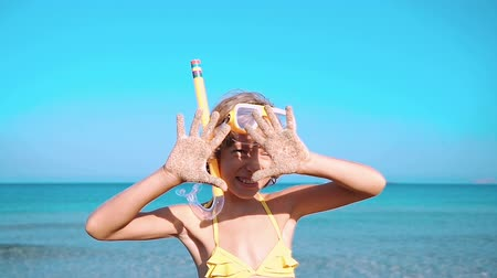 emoção : Happy child playing on the beach. Kid showing sand on hands. Summer vacations concept