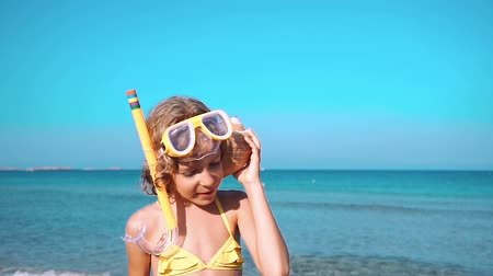 Happy child listen seashell on the beach. Portrait of girl against blue sea and sky background. Kid having fun on summer vacation. Dream and imagination concept