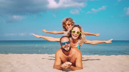 Happy family lying on the beach. People having fun on summer vacation. Father, mother and child against blue sea and sky background. Holiday travel concept