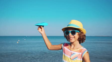 Happy child playing with paper airplane against sea and sky background. Kid pilot having fun outdoor. Summer vacation and travel concept. Freedom and imagination