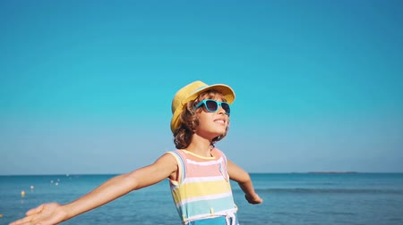 Happy child with open hands against blue sea and sky background. Kid having fun on summer vacation. Freedom and imagination concept 影像素材