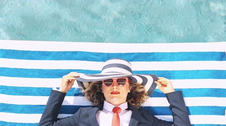 Successful young businesswoman on the beach. Woman lying on striped towel near swimming pool. Summer vacations and freedom travel concept