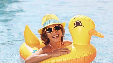 gülümsüyor : Happy child having fun on summer vacation. Funny kid in swimming pool. Active healthy lifestyle concept