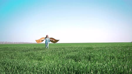 Happy child playing with toy paper wings. Pilot in green spring field. Kid having fun against summer sky background. Summer travel and vacation concept