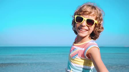 um : Happy child with open hands against blue sea and sky background. Kid having fun on summer vacation. Freedom and imagination concept Stock Footage