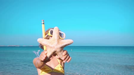 Happy child playing on the beach. Kid showing sea star. Summer vacations concept Wideo