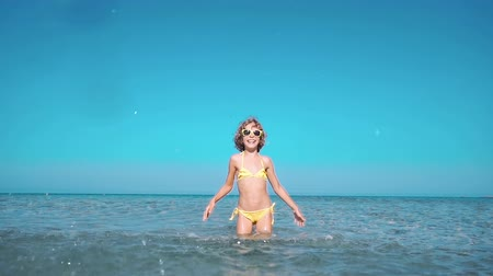 Happy child playing in the sea. Kid having fun at the beach. Summer vacation and active lifestyle concept