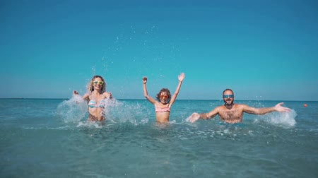 Happy family having fun on summer vacation. Father, mother and child playing in sea. Active healthy lifestyle concept