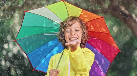 Happy child playing in the rain. Little girl with umbrella having fun outdoor in spring park