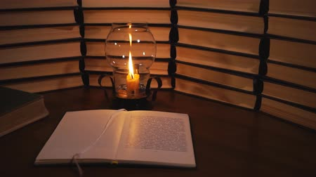Open book and a burning candle. Reading a book by candlelight Стоковые видеозаписи