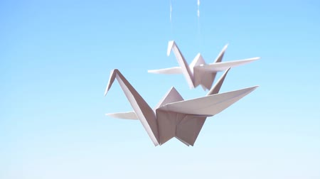 Origami crane. Origami birds on a blue sky background
