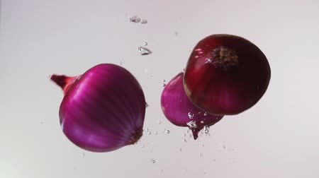 Red onions falling into water on white background. Slow motion close up