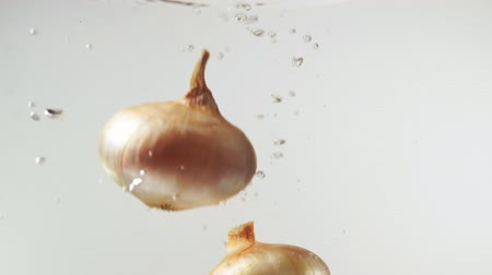 Slow motion: yellow onion falling into water, white background