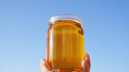 A honey jar against a blue sky background. The beekeeper keeps a jar of honey in his hand