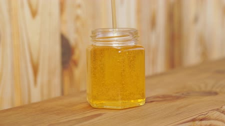 Honey is poured into a glass jar on a wooden background