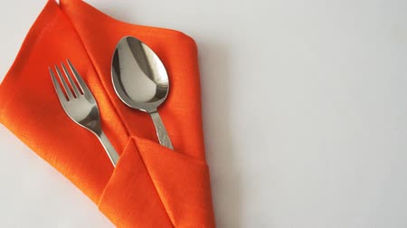 столовые приборы : Fork and spoon. Fork and spoon in textile napkin on table Стоковые видеозаписи