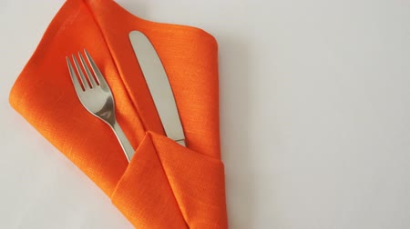 Knife and fork. Knife and fork in textile napkin on table Стоковые видеозаписи