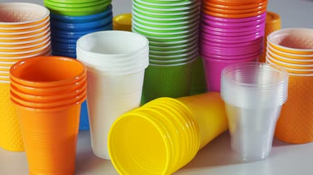 Disposable cups. Stack of colorful plastic cups on the table Стоковые видеозаписи