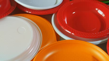ware : Disposable plates. Stack of colorful plastic plates on the table. Rotation. Closeup