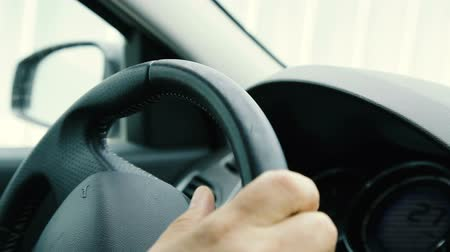 Hand on the steering wheel. Close-up