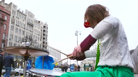 A street musician in a clown costume plays on a drum set. Slow Motion Стоковые видеозаписи