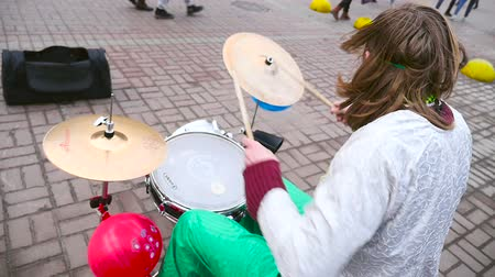 A street musician plays on a drum set. Slow-motion filming. Funny musician in clown costume