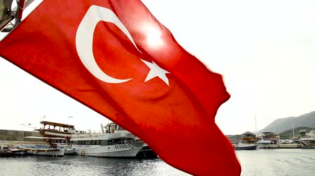 Flag of Turkey against the background of the sea. The sun shines through the flag. Develops in the wind