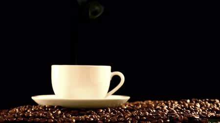 hot beverage : Coffee cup standing on beans close-up Stock Footage