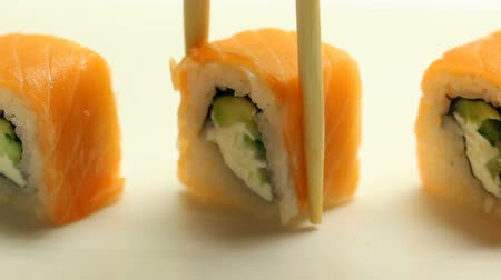 comida japonesa : Taking japanese sushi rolls with chopsticks close-up