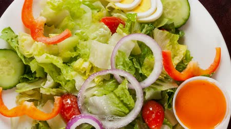 foods : Delicious garden salad served in a restaurant, fresh green salad with lettuce,cherry tomatoes,boiled egg,onions,pepper,french dressing and cucumbers