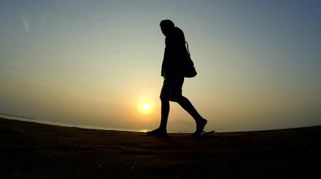 одиноко : Silhouette of man walking along on the beach while at sunset. Стоковые видеозаписи