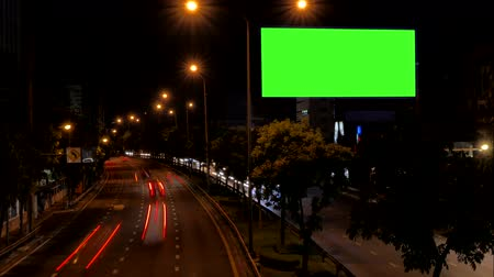 bab : Green screen of blank advertising billboard beside road with traffic at night, for advertisement , time lapse.
