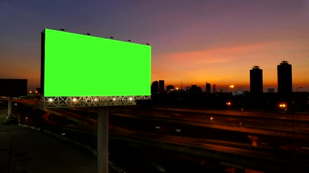 гласность : 4K of Advertising billboard, green screen, at sunset near expressway. time lapse. Стоковые видеозаписи