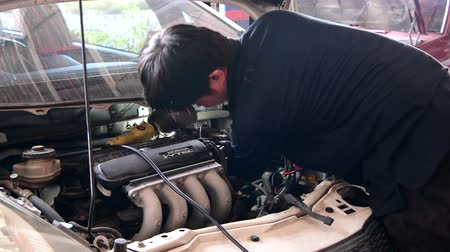 csavarkulcs : Asian mechanic man checking and maintenance car engine valve in garage.