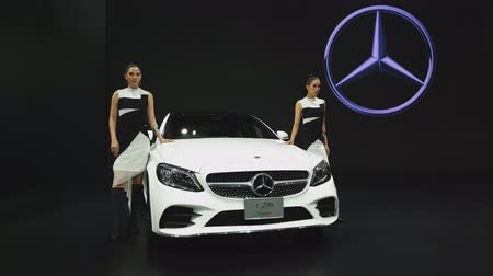 двухместная карета : NONTHABURI - NOVEMBER 28: Unidentified model with Mercedes-Benz C 200 Coupe car on display at The 35th Thailand International Motor Expo on November 28, 2018 in Nonthaburi, Thailand.