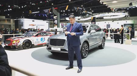 двухместная карета : NONTHABURI - NOVEMBER 28: Unidentified businessman with Bentley Bentayga car on display at The 35th Thailand International Motor Expo on November 28, 2018 in Nonthaburi, Thailand. Стоковые видеозаписи