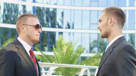 discussão : Businessmen talking near the office building