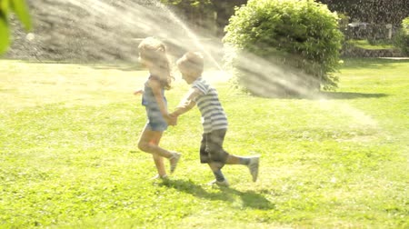 houpavý : Kids are playing in a park with sprinklers.