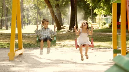 houpavý : Little boy and little girl are swinging on a swing.